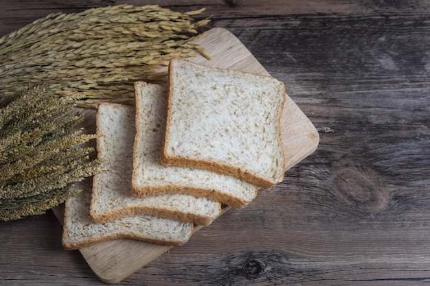Whole wheat bread or wholemeal bread on wood table with ear of paddy