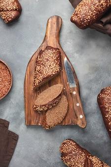 Хлеб из цельной пшеницы с кунжутом, разделочная доска на сером фоне камня. вид сверху с копией пространства. flatlay.