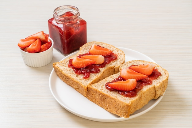 Whole wheat bread with strawberry jam and fresh strawberry