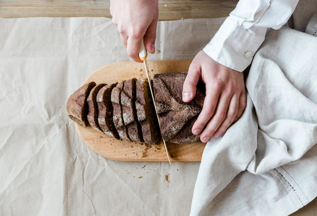 Whole wheat bread on the wooden board and knife.the man slices bread.homemade freshly baked bread.healthy food.top view.