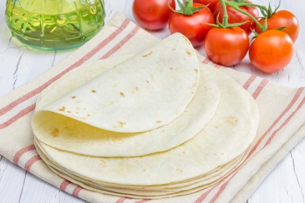 トマトと背景にオリーブオイルと全粒小麦の小麦粉のトルティーヤ