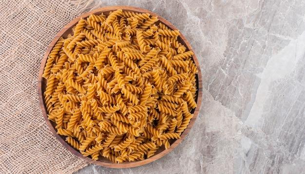黄麻布、大理石の木製プレート上の全粒小麦のフジッリ。