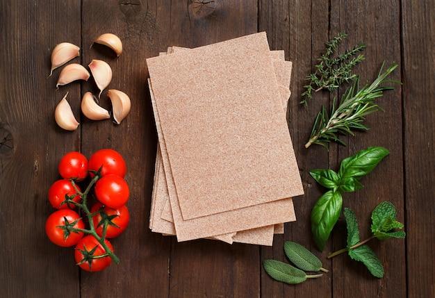 木製の背景に全粒小麦のラザニアシート、野菜、ハーブ