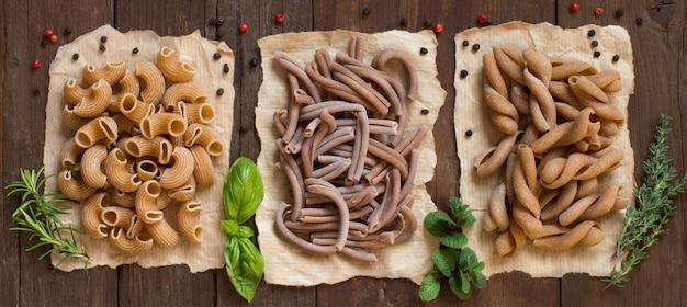 全粒小麦のパスタとハーブの茶色の木製のテーブルトップビュー