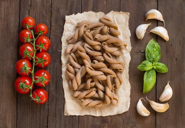 全粒小麦のパスタ、トマト、バジルの茶色の木製テーブルトップビュー