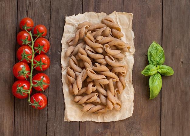 全粒小麦のパスタ、トマト、バジルの木製テーブルトップビュー