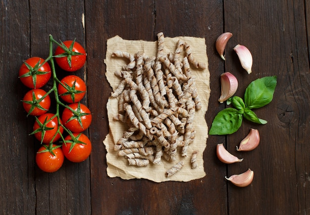 全粒小麦のパスタ、トマト、バジル、ニンニクの木製の背景