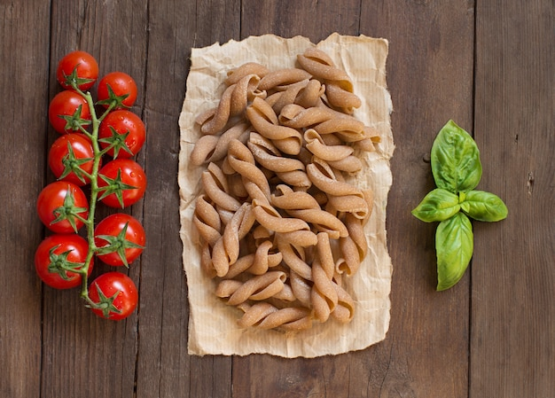 Whole wheat pasta, tomatoes and basil on wooden table top view