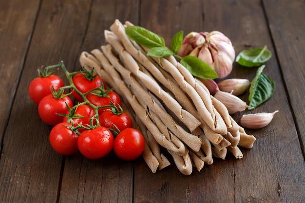 木製のテーブルに全粒小麦のパスタ、野菜、ハーブ