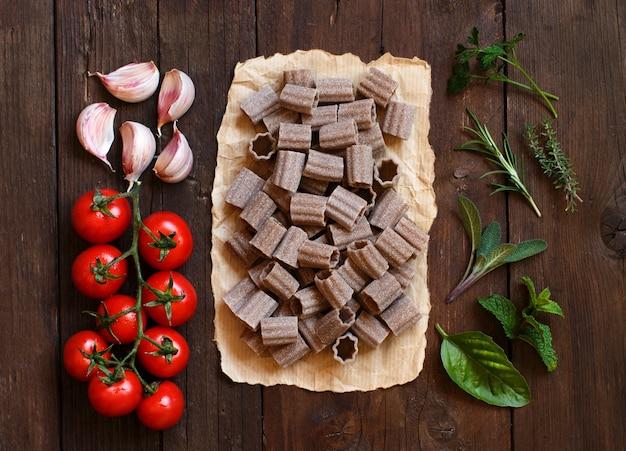 全粒小麦のパスタ、野菜、ハーブソンの木製の背景
