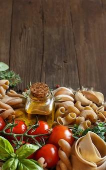 全粒粉パスタ、野菜、ハーブ、木製のテーブルにオリーブオイルをコピースペースでクローズアップ