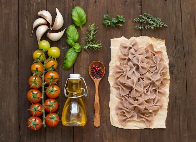 全粒小麦のパスタ、野菜、ハーブ、木製の背景にオリーブオイル