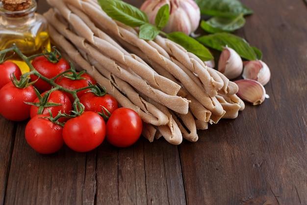 全粒小麦のパスタ、野菜、ハーブ、オリーブオイルを木製のテーブルに