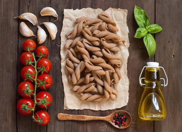 全粒小麦のパスタ、野菜、ハーブ、オリーブオイルの木製のテーブルの上から見る
