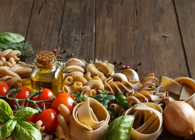 Whole wheat pasta, vegetables,  herbs and olive oil on wooden table close up with copy space