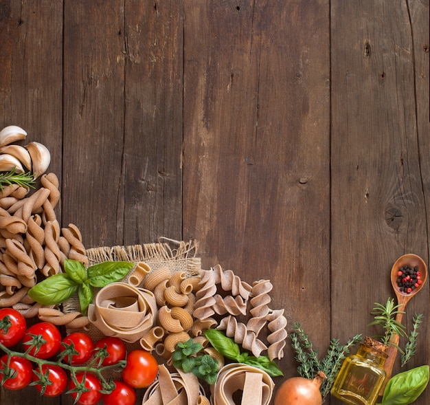 Whole wheat pasta, vegetables, herbs and olive oil on wooden table top view with copy space