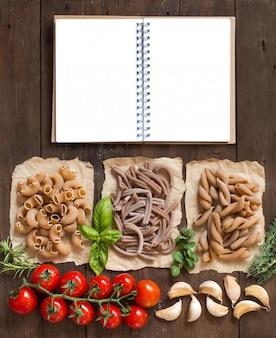 ハーブと野菜の木製のテーブル、トップビューで全粒小麦のパスタ