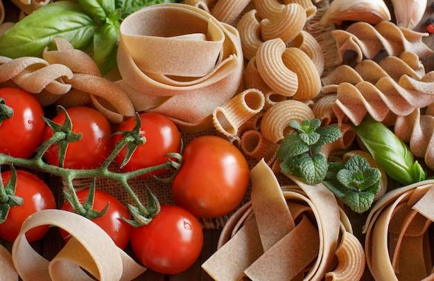 野菜とハーブの木製のテーブルで全粒小麦のパスタをクローズアップ