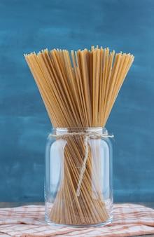 Спагетти из цельной пшеницы в банке, на полотенце, на мраморной поверхности.