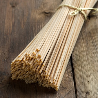 Whole wheat spaghetti on the old wooden table