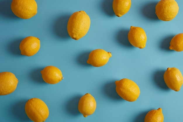 Whole yellow lemons full of vitamins and antioxidants, have sour taste, isolated over blue studio background. essential ingredient for your nutrition. useful peel containing bioactive compounds