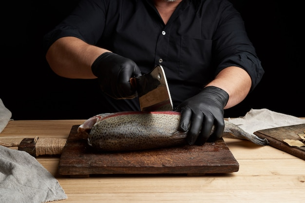 黒いシャツと黒いラテックス手袋のシェフが新鮮な魚のwhole全体をスライス