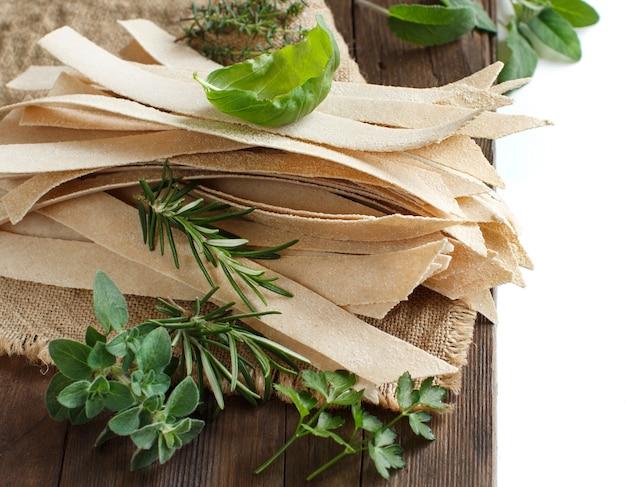 Цельнозерновые ремесленные макароны и травы на старом деревянном столе крупным планом