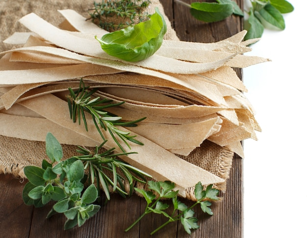 Цельнозерновые ремесленные макароны и травы на старом деревянном столе