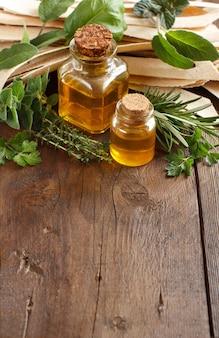 Цельнозерновые ремесленные макароны, оливковое масло и травы на старом деревянном столе