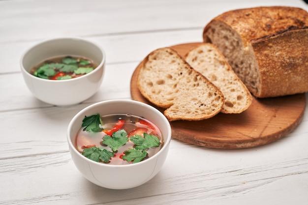 Цельнозерновой хлеб и миска супа на деревянном столе