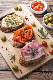 Цельнозерновые хлеб бутерброды с сыром, беконом и оливками консервированные перцы с помидорами на деревянных фоне.