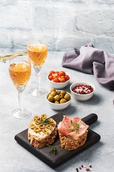 Wholegrain bread sandwiches with cream cheese, bacon and olives on a wooden cutting board. a glass of white wine.