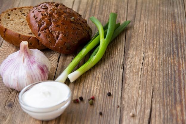Wholegrain bread, sour cream, onion and garlic on a wooden background