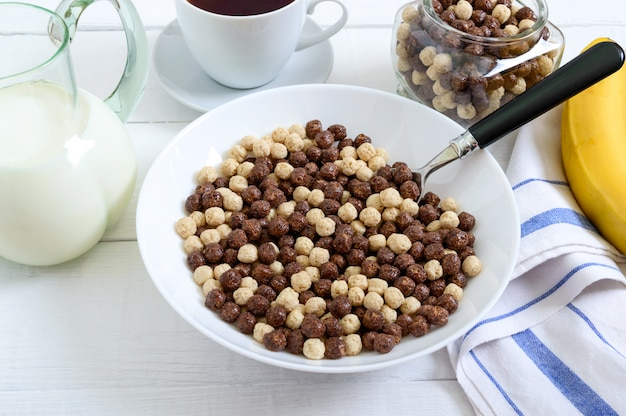 Wholegrain chocolate and milk balls, fruit, tea and milk on white wooden surface. healthy cereal breakfast. baby breakfast. baby eating. balanced diet.