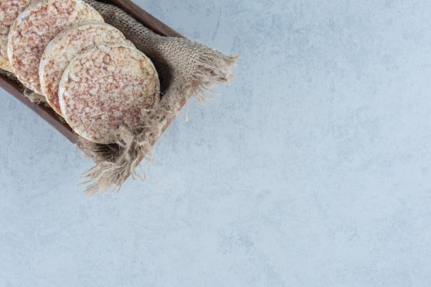Fette biscottate integrali su tovagliolo nella scatola su marmo.