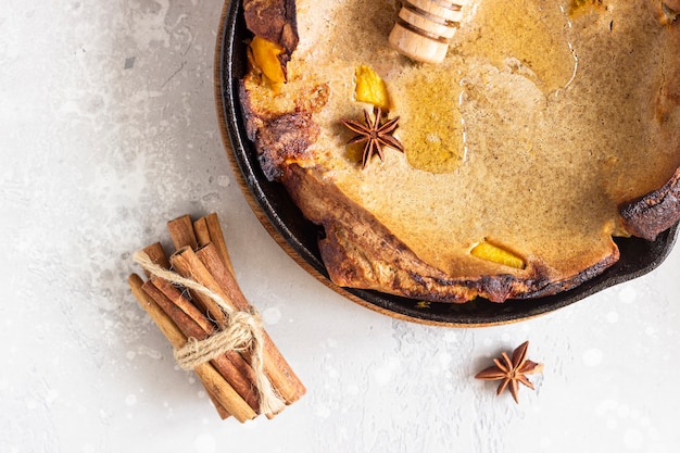 Wholegrain dutch baby with apple, honey and spices (cinnamon and anise). delicious autumn or winter breakfast.