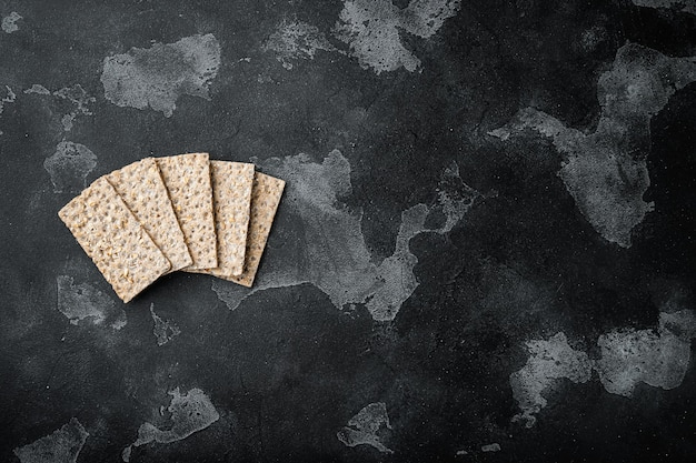 Wholegrain rye crispbread cracker set, on black dark stone table, top view flat lay
