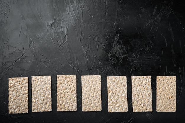 Wholegrain 호밀 crispbread 크래커 세트, 검은 어두운 돌 테이블 배경, 상위 뷰 평면 누워, 텍스트 복사 공간