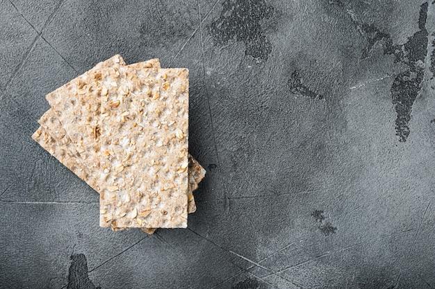 Набор крекеров из цельнозерновых ржаных хлебцев на сером каменном столе