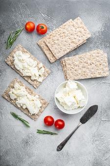 회색 돌 테이블에 크림 치즈 세트가있는 wholegrain rye crispbread, 평면도 평면 배치
