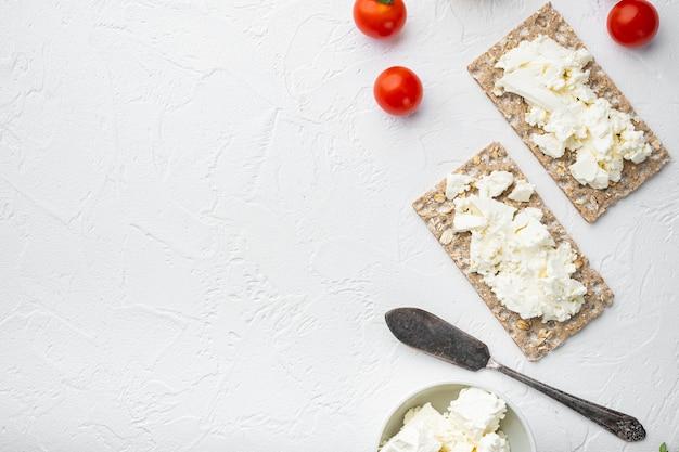 Ржаные цельнозерновые хлебцы с набором сливочного сыра на белом каменном столе