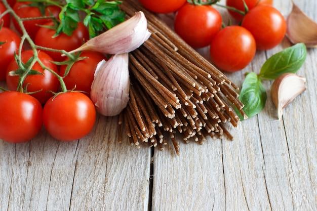 Wholegrain rye spaghetti, tomatoes and herbs on wood