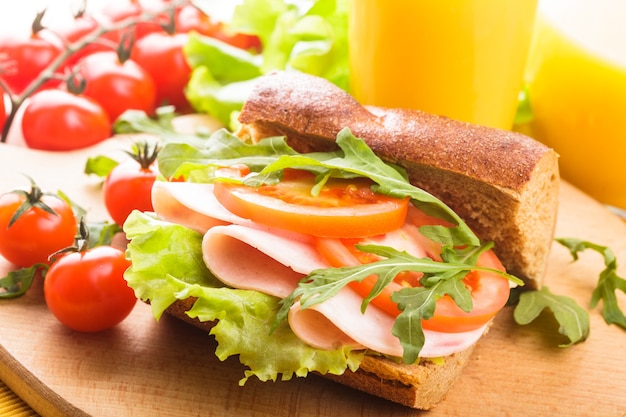 Цельнозерновой бутерброд с ветчиной, помидорами, латте и рукколой со стаканом апельсинового сока. завтрак