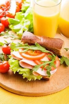 Цельнозерновой бутерброд с ветчиной, помидорами, латте и рукколой со стаканом апельсинового сока на доске