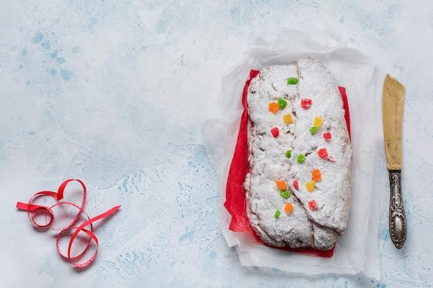 Цельнозерновой штоллен с изюмом и сахарной пудрой на льняной салфетке с ситом, красная лента поверх голубого снежного бетона. традиционный немецкий рождественский торт. вид сверху.