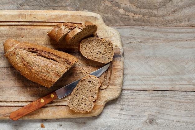 Хлеб из непросеянной муки на вид сверху деревянный стол