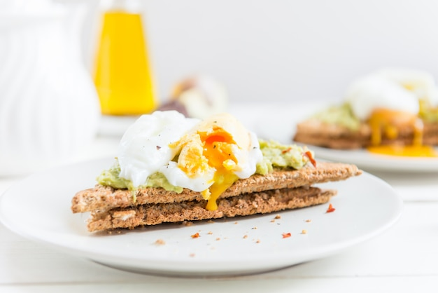 Wholemeal bread toast and poached egg with mashed avocado and ch