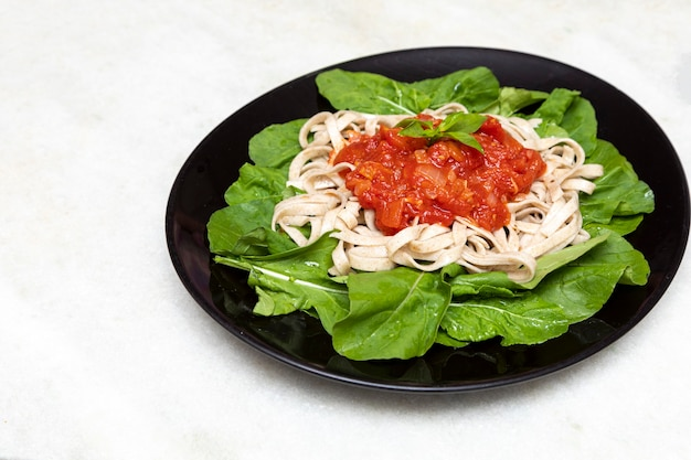 Паста из непросеянной муки с зелеными листьями рукколы, красным соусом и бальзамическим уксусом на черной тарелке и белом мраморе