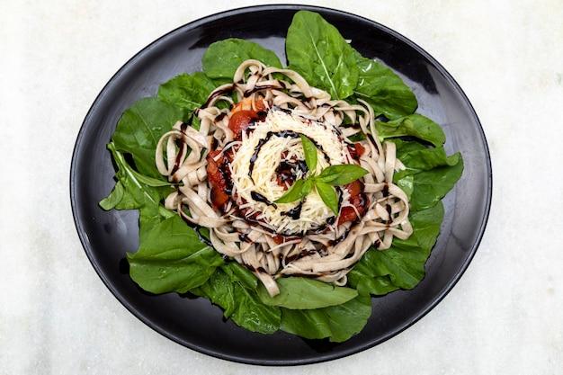 パルメザンチーズ、ルッコラの緑の葉、赤いソース、黒いプレートと白い大理石の背景にバルサミコ酢を添えた全粒粉パスタパスタ