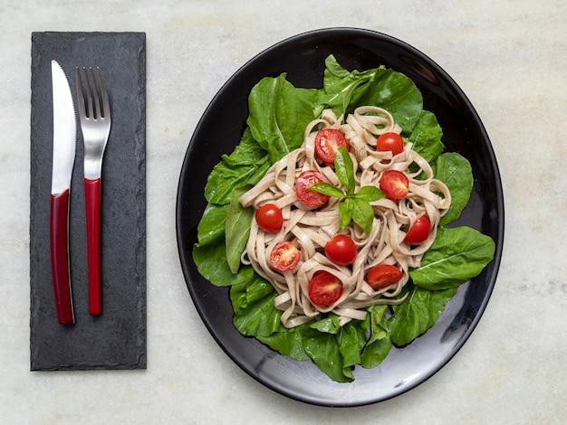 Паста из непросеянной муки с зелеными листьями рукколы и помидорами черри на черной тарелке и белом мраморе